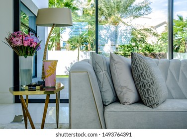 HAMALA, BAHRAIN - MARCH 02, 2019: Interior view of detail of a side table and gray silk upholstered couch in the living room of a luxury Middle Eastern villa development.