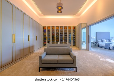 HAMALA, BAHRAIN - MARCH 02, 2019: The closets in a bespoke dressing room of a luxury Middle Eastern villa development showing the bedroom in the background.