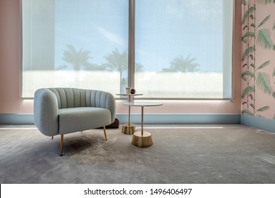 HAMALA, BAHRAIN - MARCH 02, 2019: Interior view of an armchair and side tables on a gray silk carpet with pink bespoke wallpaper in the bedroom of a luxury Middle Eastern villa development.