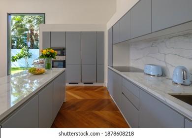 HAMALA, BAHRAIN - MARCH 02, 2019: Elegant modernist kitchen with a wooden floor in a luxury villa.
