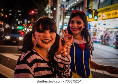 HAMAMATSU, JAPAN - OCTOBER 31, 2013:2 Japanese Girls with Gothic Makeup Smiling with V sign at Shopping Street Crowded with People Wearing Fancy Ghost Costumes or Spooky Cosplays to Celebrate Halloween