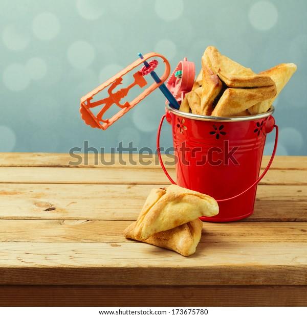 Hamantaschen cookies in bucket with grogger noise maker