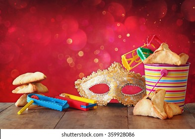 Hamantaschen cookies or hamans ears,noisemaker and mask for Purim celebration (jewish carnival holiday) and glitter background. selective focus