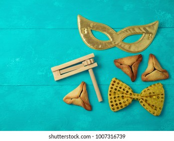 Hamantaschen cookies on white table with mask and noise maker. Purim holiday celebration. Top view