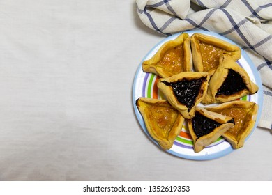 Hamantash Purim blueberry and apricot jam cookies on colored plate with a plaid blue rag and a white sheet background