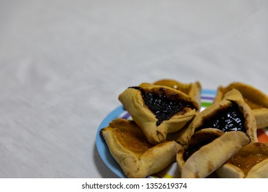 Hamantash Purim blueberry and apricot jam cookies on colored plate with white sheet background