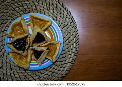 Hamantash Purim blueberry and apricot jam cookies on colored plate with wooden table background