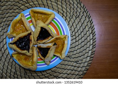 Hamantash Purim blueberry and apricot jam cookies in colored plate with wooden table background