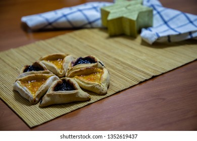 Hamantash Purim blueberry and apricot jam cookies with wooden table background and David star shape candle
