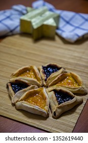 Hamantash Purim blueberry and apricot jam cookies with wooden table background