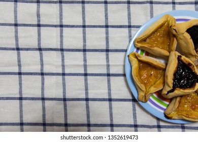 Hamantash Purim Blueberry and apricot jam cookies on colored plate on tablecloth with blue squares background