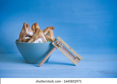 Hamantashen and Purim toy noisemaker on blue background with copy space. Jewish holiday Purim concept.
