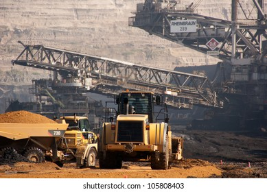 HAMBACH, GERMANY - SEPTEMBER 1: Power-shovels and one of the world's largest excavators (background) digging lignite in of the world's deepest open-pit mines in Hambach on September 1, 2010.