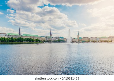 Hamburg cityscape on sunny day against blue sky with Alster lake and fountain in foreground