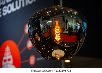 Hamburg / Germany - 09 05 2018: International maritime trade fair SMM 2018. Maritime business exhibition in Hamburg Germany. Reflection in mirror glass lampshade with incandescent lamp spiral inside