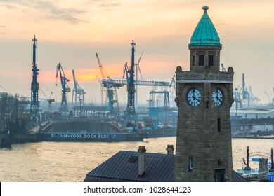 HAMBURG, GERMANY - 1 JANUARY 2015: The tower of the river station with a clock against the backdrop of Elbe River and the port cargo terminal, on first day of the year.