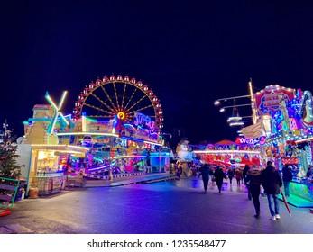 Hamburg, Germany - 18. November 2018. View of the Hamburg DOM amusement park, ferris wheel and walking people. Amusement park in the evening.