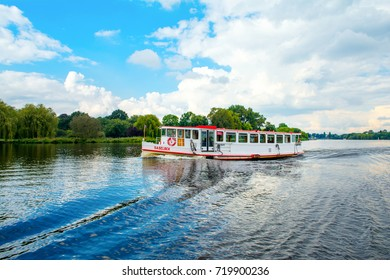 Hamburg, Germany - 18 September 2017: Traditional steamer boat for cruise on the water of Lake Alster with cloudy autumnal landscape on background