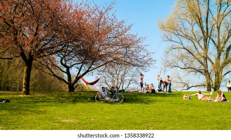 Hamburg, Germany - April 2018: Young people welcoming and celebrating the spring in the city park of Hamburg, Germany.
