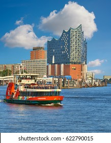 HAMBURG, GERMANY- AUGUST 13, 2015: Boat with tourists goes on Elbe river in Hamburg with The Elbphilharmonie is a concert hall in the HafenCity.