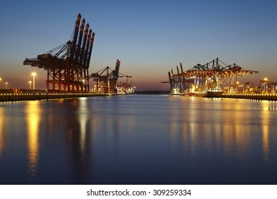 HAMBURG, GERMANY - AUGUST, 22. The terminals of Eurogate and Burchardkai in the deepwater port Hamburg Waltershof in the evening at the point of the blue hour on August 22, 2015.
