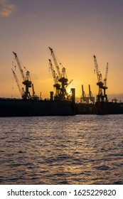Hamburg, Germany. Cranes silhouetted against the evening sky in the harbor at dusk. The Port of Hamburg (German: Hamburger Hafen) is a sea port on the river Elbe. It is Germany's largest harbor.