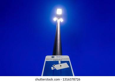 Hamburg, Germany - February 3, 2019: A police surveillance camera warning sign on a lamp post at night.