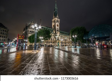 HAMBURG, GERMANY - JULY 10, 2018: Hamburg City Hall is the seat of local government of the Free and Hanseatic City of Hamburg, Germany. Amazing reflections on the ground. Wet nasty weather.