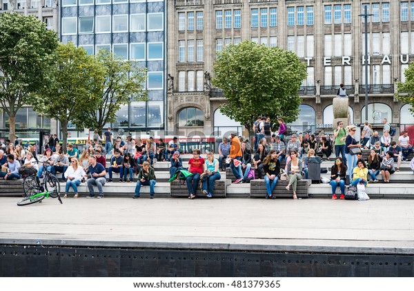 HAMBURG, GERMANY - JULY 30, 2016: City Center  People walking on Shopping Boulevard Jungfernstieg and sitting in front of Alster Lake on a summer day
