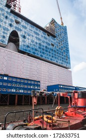 Hamburg, Germany - June 16th, 2013: old ship in front of the construction-site of the Elbe Philharmonic Harmony. The still unfinished building is a financial Desaster in Germany.