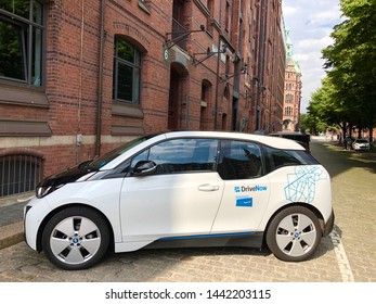 Hamburg, Germany - June 21, 2019: A BMW i3 electric car by the car sharing company Drive Now is standing in front of an old storage building in the famous Hafencity in Hamburg. 'DriveNow' is a car
