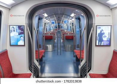 Hamburg, Germany - June 22, 2020: Interior of an empty metro rail car  / subway train (U-Bahn). Straight view along the main aisle. Part of Hamburg's public transportation network (Hochbahn)