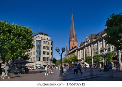 Hamburg, Germany - June 29, 2019: People walking in shopping street Monckebergstrasse and the tower of St. Petri, or Saint Peter church in Hamburg, Germany on June 29, 2019