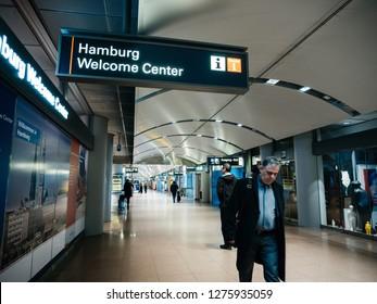 HAMBURG, GERMANY - MAR 20, 2018: Adult man walking under the sign Hamburg Welcome Center tourist info point inside Hamburg airport