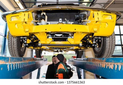 Hamburg, Germany - March 02, 2019: Car inspector inspects a vintage car on the lifting platform in the car repair shop - Serie Repair Workshop