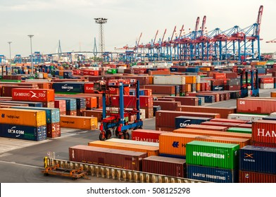 Hamburg, Germany - May 10, 2011: A straddle carrier is serving containers at the Buchardkai Container Terminal in Hamburg. In the background you can see the famous Kohlbrand bridge connecting the