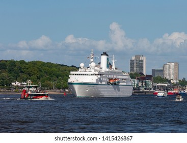HAMBURG, GERMANY - MAY 12, 2019: The 175 meter long cruise ship MS Deutschland leaving Hamburg harbour on a sunny spring day after attending the annual Hamburg harbour festival of 2019.