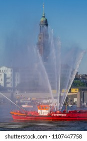 Hamburg, Germany - May 13, 2018: A historic fire extinguishing boat at the Harbor Birthday festivity with St. Michael's Church (St. Michaelis) in the background.