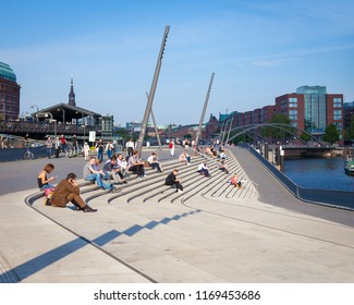 Hamburg, Germany - May 2018: People hanging out at the steps near the port of Hamburg during a sunny afternoon