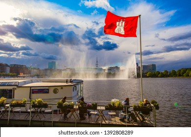 HAMBURG, GERMANY - May 2019: People sitting in outdoor cafe by the Alster Lake in Hamburg in the central historical district Roterbaum of Hamburg, Germany. Sunny day in Hamburg.