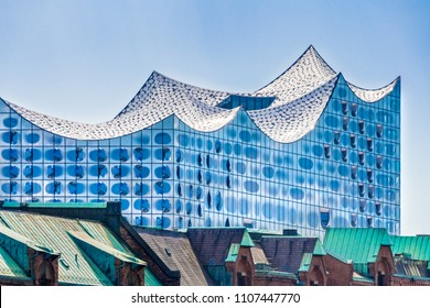 Hamburg, Germany - May 26, 2018: The Concert Hall Elbphilharmonie behind the roofs of the historic warehouse district (German: Speicherstadt).