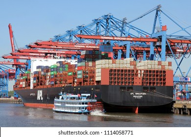 HAMBURG, GERMANY - MAY 4, 2018: The Container ship APL SINGAPURA and the Replica Paddle Steamer LOUISIANA STAR at the maritime container port Terminal Burchardkai