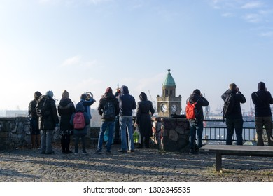 Hamburg, Germany -November 17, 2018: Tourists look at the harbor scene to the landing bridges