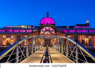 """Hamburg, Germany - November 2, 2018: The venue """"Fischauktionshalle"""" in Hamburg, Germany, is a former fish auction hall in the harbor. At dusk it is colorfully illuminated."""