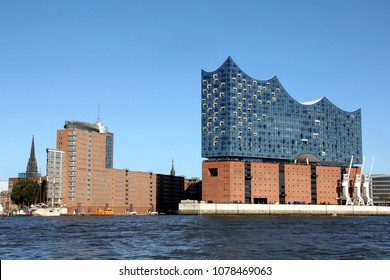 HAMBURG, GERMANY - OCTOBER 1, 2017:  Elbe Philharmonic Hall (Elbphilharmonie) with the neighboring storehouse district Speicherstadt and the church spire of St. Nikolai Memorial seen from South West