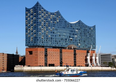 HAMBURG, GERMANY - OCTOBER 1, 2017:  Elbe Philharmonic Hall (Elbphilharmonie) seen from South West with police boat passing in front
