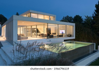 Hamburg, Germany – October 14, 2019: Luxurious villa with swimming pool. External view of a contemporary house. Dusk shot