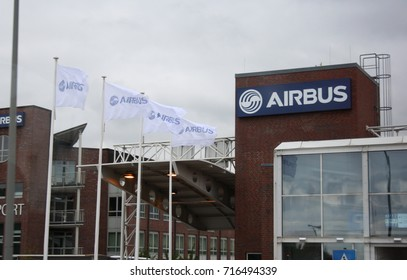 HAMBURG, GERMANY – SEPTEMBER 26 2015: Outside Airbus' Finkenwerder manufacturing facility in Hamburg, Germany, with Airbus flags flying high at the front entrance.