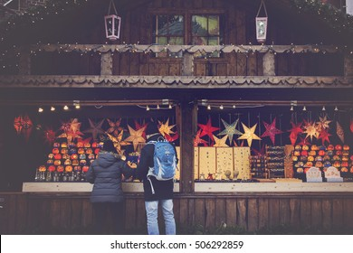 Hamburg, Germany, street Christmas market stall - A couple watching offerings at Xmas market - Christmas markets decorations