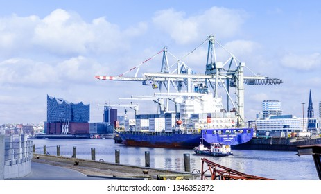 Hamburg, Germany-2. April 2018: container ship in Hansa harbor is loaded, in the background the elbphilharmonie